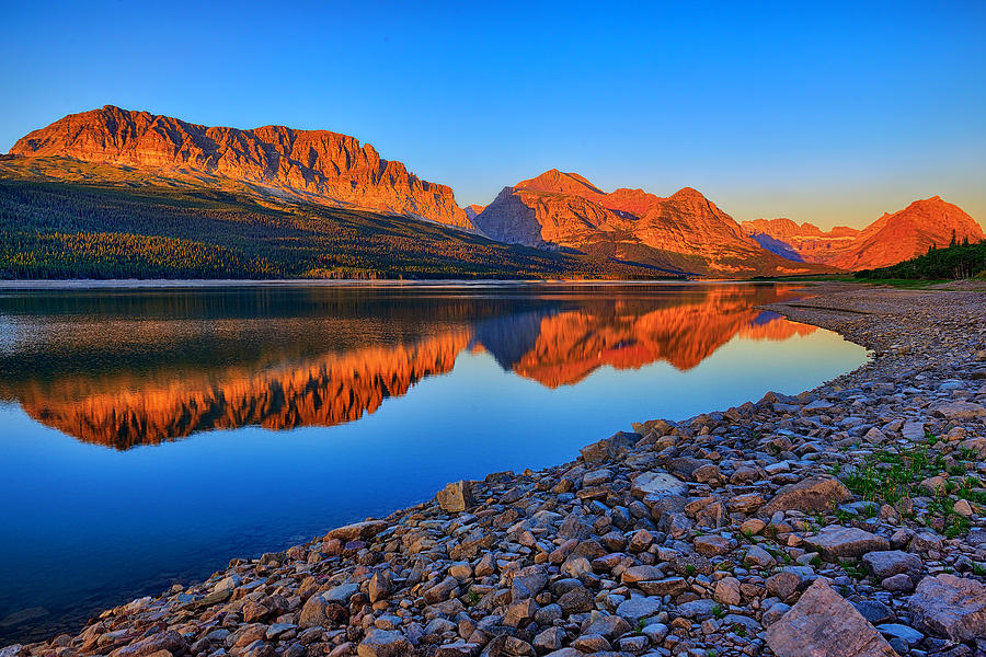 First light of the morning along a still Lake Sherburne in Glacier National Park