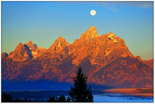 Alpenglow light on the Tetons with a setting full moon