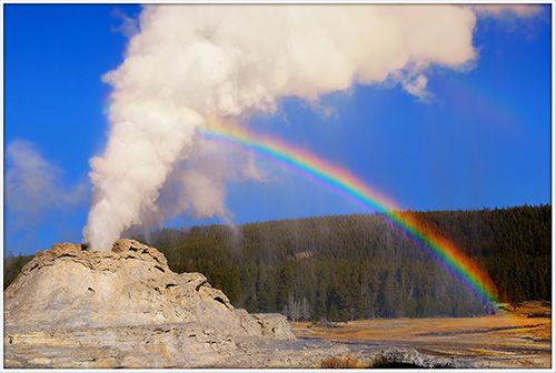 Castle Geyser eruption with rainbow